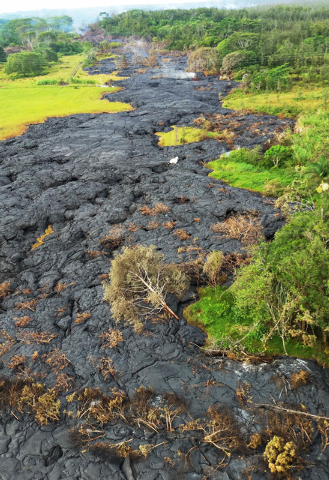 This Oct. 28, 2014 photo provided by Pete Stachowicz of Paradise Helicopters shows a lava flow near the town of Pahoa on the Big Island of Hawaii. The National Guard is deploying troops to the rur ...