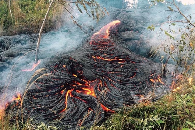 This Oct. 30, 2014 photo provided by the U.S. Geological Survey shows lava flow burning vegetation near the town of Pahoa on the Big Island of Hawaii. The Hawaii National Guard is deploying troops ...
