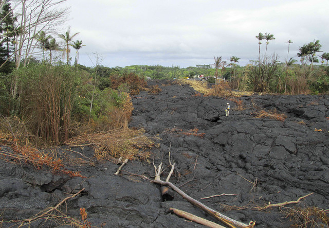 The lava flow from the Kilauea Volcano that began on June 27 moves near the Pahoa cemetery looking northeast toward houses on Pahoa Village Road on the Big Island of Hawaii, Nov. 9, 2014. Official ...