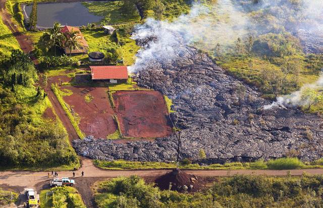This Monday, Nov. 10, 2014 photo released by The County of Hawaii via Ena Media Hawaii/Blue Hawaiian Helicopters shows lava flow from the Kilauea Volcano near a residential structure in Pahoa, Haw ...