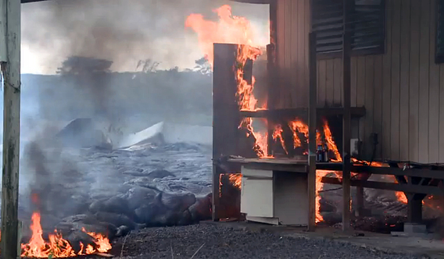 In this image made from video provided by the County of Hawaii, lava flow from the Kilauea Volcano burns a residential structure Monday, Nov. 10, 2014, in Pahoa, Hawaii. A stream of lava set a hom ...