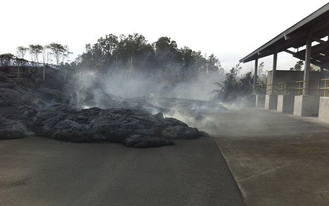 In this Nov. 13, 2014 photo provided by the U.S. Geological Survey, lava flow from the Kilauea Volcano that began on June 27 approaches the Pahoa transfer station in Pahoa, Hawaii. The county says ...