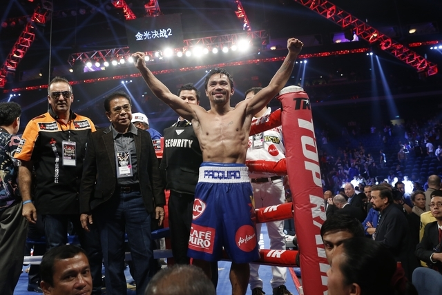 WBO welterweight champion Manny Pacquiao, center, celebrates after defeating WBO junior welterweight champion Chris Algieri of the United States during their welterweight title boxing match at the ...