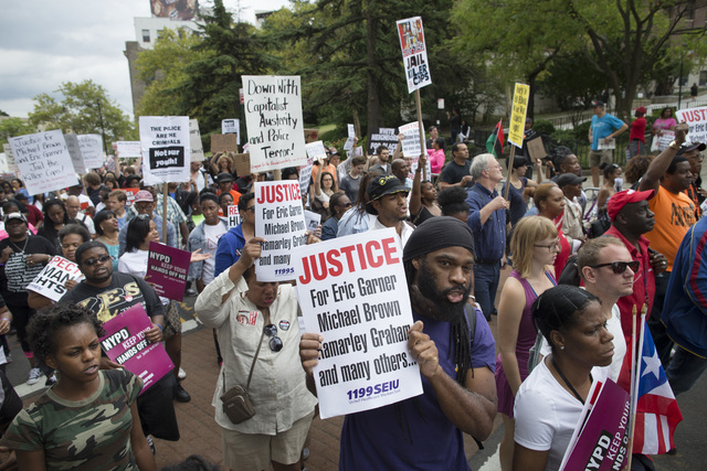 Demonstrators march to protest the death of Eric Garner, Saturday, Aug. 23, 2014, in the Staten Island borough of New York. A lawyer says a grand jury in New York City has declined to indict a whi ...