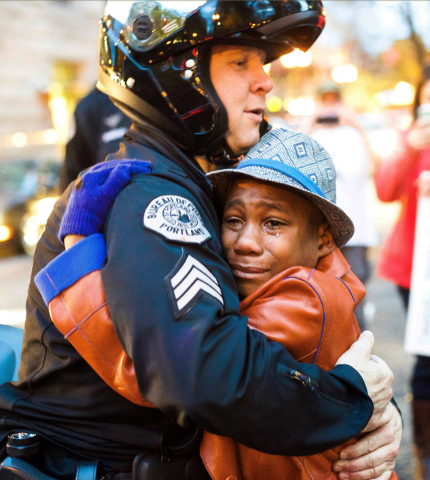 In this Tuesday, Nov. 25, 2014 photo provided by Johnny Nguyen, Portland police Sgt. Bret Barnum, left, and Devonte Hart, 12, hug at a rally in Portland, Ore., where people had gathered in support ...