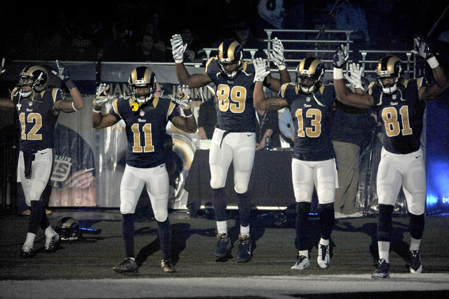 Members of the St. Louis Rams raise their arms in awareness of the events in Ferguson, Mo.,  as they walk onto the field during introductions before an NFL football game against the Oakland Raider ...