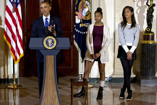 In this Nov. 26, 2014 file photo, President Barack Obama, joined by his daughters Malia, right, and Sasha, center, speaks at the White House, in Washington during the presidential turkey pardon ce ...