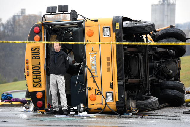 Authorities work the scene of an accident involving two school buses in Knoxville, Tenn., Tuesday, Dec. 2, 2014. (AP Photo/Knoxville News Sentinel, Michael Patrick)