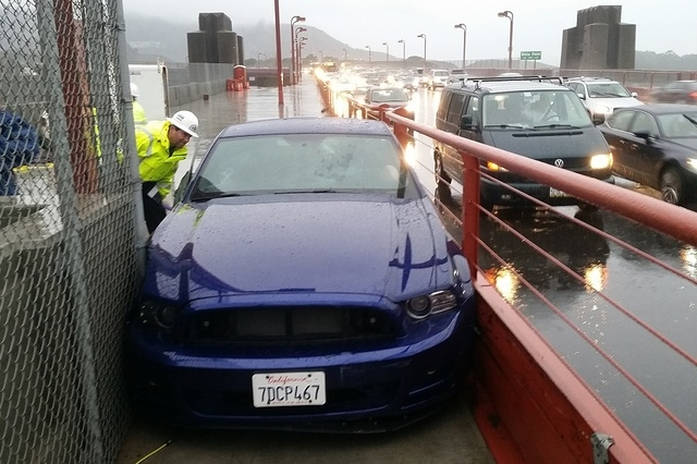 In this photo released by the Golden Gate Bridge Highway and Transportation District, a bridge worker looks over a car driven onto the pedestrian walkway of the Golden Gate Bridge, Tuesday, Dec. 2 ...