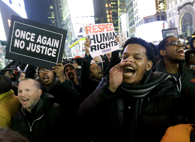 Protestors shout at Times Square after it was announced that the New York City police officer involved in the death of Eric Garner is not being indicted, Wednesday, Dec. 3, 2014, in New York. A gr ...