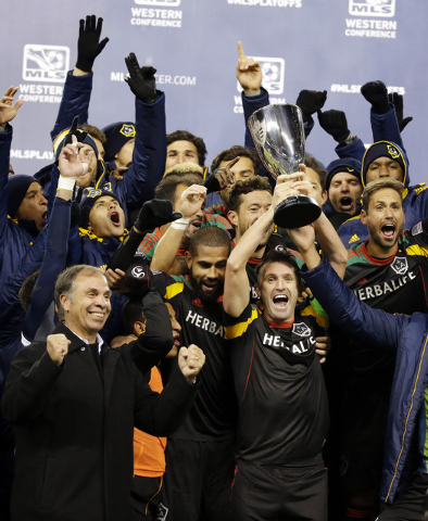 Los Angeles Galaxy head coach Bruce Arena, lower left, cheers as Los Angeles Galaxy's Robbie Keane, center, lifts up the western conference trophy after the Galaxy beat the Seattle Sounders, Sunda ...
