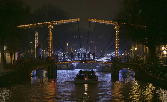 "In this Saturday, Nov. 29, 2014 file photo, people stand on an illuminated historic drawbridge to look at the ""Lightbridge"" sculpture by Dutch Frank Tjepkema, rear, in Amsterdam. The sculpture is  ..."