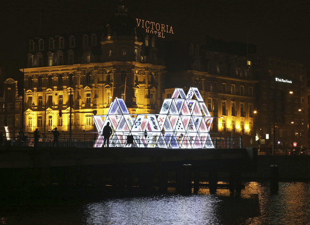 "In this Saturday, Nov. 29, 2014 photo, people look at a light sculpture called, ""House of Cards,"" by OGE Creative Group, from Israel, near Central Station in Amsterdam. The sculpture is  ..."