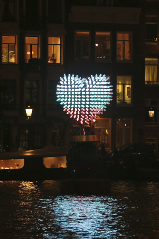 "In this Saturday, Nov. 29, 2014 photo, a light sculpture titled, ""178 BOTTLES, 1 MESSAGE,"" by Dutch Saskia Hoogendoorn and Lieuwe Martijn Wijnands, consisting of 178 bottles with LED lig ..."