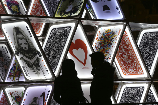 "In this Saturday, Nov. 29, 2014 photo, a couple looks at a light sculpture called, ""House of Cards,"" by OGE Creative Group, from Israel, near Central Station in Amsterdam. The sculpture  ..."