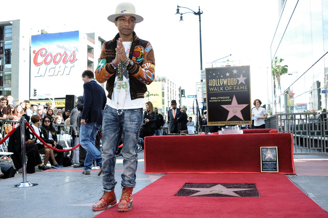Pharrell Williams attends the ceremony honoring him with a star on the Hollywood Walk of Fame on Thursday, Dec. 4, 2014, in Los Angeles. Williams received a Grammy nomination for urban contemporar ...