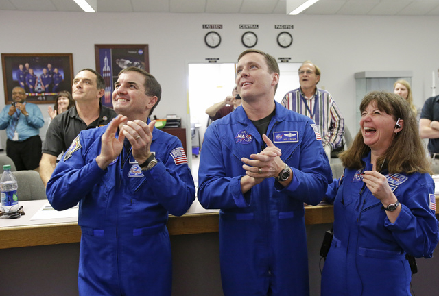 NASA astronauts, from left, Rex Walheim, Jack Fischer and Cady Coleman, cheer as they watch the landing of the Orion test flight on a television at the Press Site at the Kennedy Space Center, Frid ...
