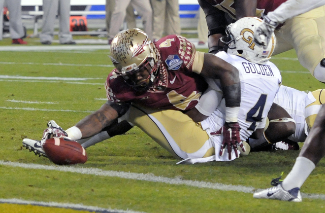 Florida State's Dalvin Cook, left, stretches the ball just short of the goal line as Georgia Tech defensive back Jamal Golden, right, defends during the first half of the Atlantic Coast Conference ...