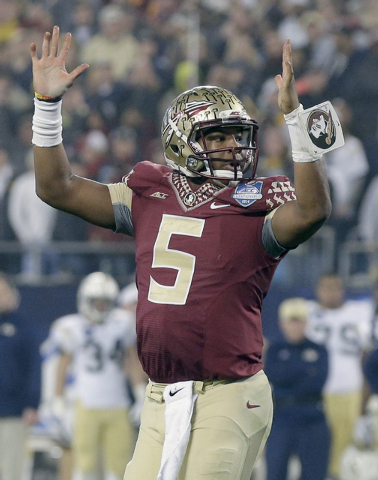 Florida State quarterback Jameis Winston (5) raises his arms after a touchdown against Georgia Tech during the first half of the Atlantic Coast Conference championship NCAA college football game i ...