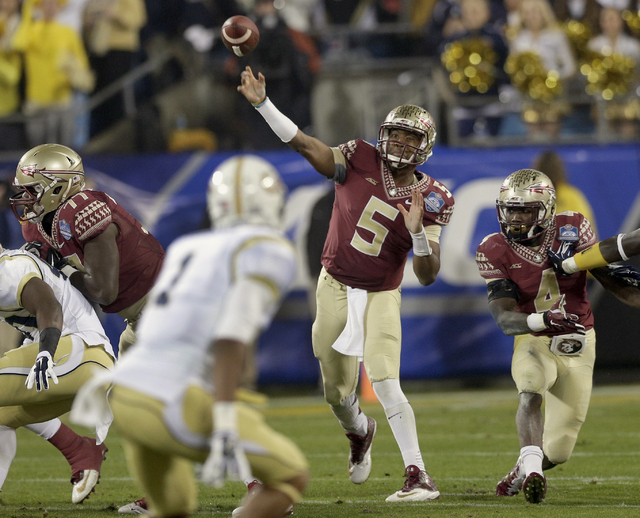 Florida State quarterback Jameis Winston (5) throws a pass against Georgia Tech during the first half of the Atlantic Coast Conference championship NCAA college football game in Charlotte, N.C., S ...
