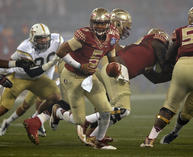 Florida State quarterback Jameis Winston (5) looks to hand off the ball against Georgia Tech during the first half of the Atlantic Coast Conference championship NCAA college football game in Charl ...