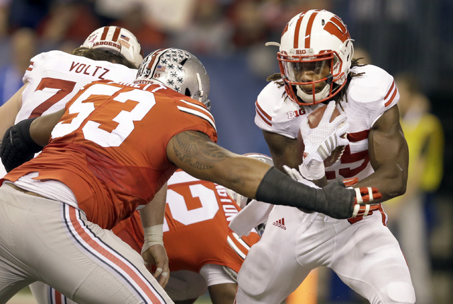 Wisconsin running back Melvin Gordon, right, runs with the ball as Ohio State defensive tackle Michael Bennett defends during the first half of the Big Ten Conference championship NCAA college foo ...