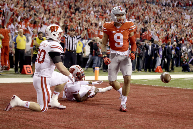 Ohio State wide receiver Devin Smith, right, celebrates after catching a touchdown pass as Wisconsin linebacker Derek Landisch, left, and Sojourn Shelton, center, watch during the first half of th ...