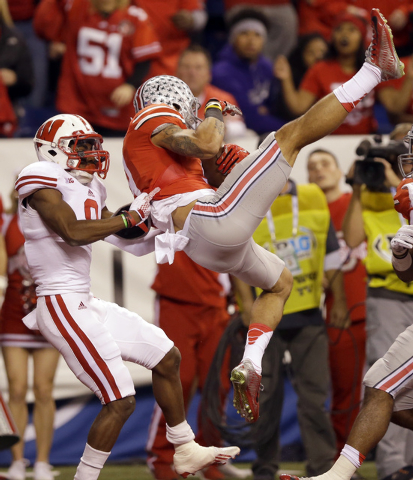Ohio State wide receiver Devin Smith, right, catches a 39-yard touchdown pass as Wisconsin cornerback Sojourn Shelton defends during the first half of the Big Ten Conference championship NCAA coll ...