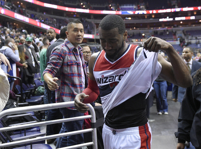 Washington Wizards guard John Wall (2) reacts after an NBA basketball game against the Boston Celtics, Monday, Dec. 8, 2014, in Washington. The Wizards won 133-132 in double overtime. (AP Photo/Ni ...
