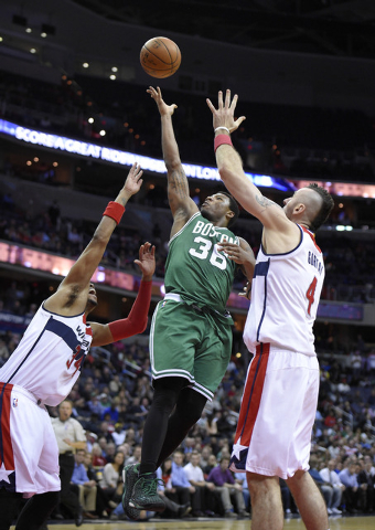 Boston Celtics guard Marcus Smart (36) goes to the basket between Washington Wizards forward Paul Pierce (34) and Marcin Gortat (4), of Poland, during the second overtime of an NBA basketball game ...