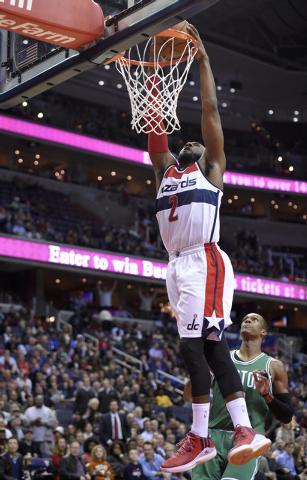 Washington Wizards guard John Wall (2) dunks over Boston Celtics guard Rajon Rondo, bottom right, during the first half of an NBA basketball game, Monday, Dec. 8, 2014, in Washington. (AP Photo/Ni ...