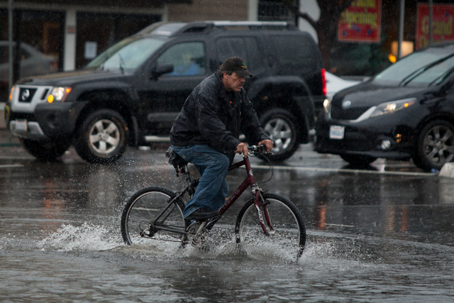 A man rides his bicycle through the flooded intersection of Airport Blvd. and Grand Ave. in South San Francisco, on Thursday, Dec. 11, 2014.  A powerful storm churned through the San Francisco Bay ...