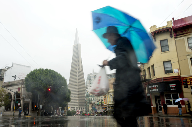A man passes the Transamerica building as rain pounds San Francisco's North Beach district on Thursday, Dec. 11, 2014. A powerful storm churned through Northern California Thursday, knocking out p ...