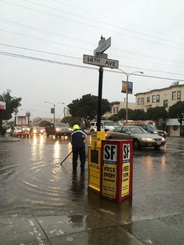 This photo provided by Yvonne Pham shows city employee working to clear the drains of a flooded San Francsico street on Thursday, Dec. 11, 2014. A powerful storm churned through Northern Californi ...