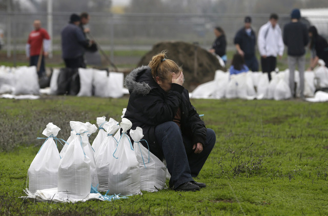 Kathryn Olson rests on a sandbag before carrying it to her vehicle to be used at her home in the Sacramento suburb of North Highlands, Calif., Wednesday, Dec. 10, 2014.  Sandbags and sand were pro ...