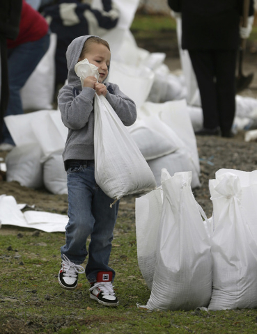 Hudson Gilbert, 4, carries a sandbag while helping his mother, Janessa Gilbert, fill sand bags at an area fire station in the Sacramento suburb of North Highlands, Calif., Wednesday, Dec. 10, 2014 ...
