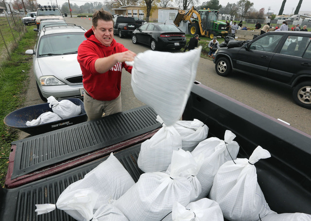 Mike Whitesone tosses a sandbag onto his pickup truck for use around his home in the Sacramento suburb of North Highlands, Calif., Wednesday, Dec. 10, 2014.  Sandbags and sand were provided in flo ...