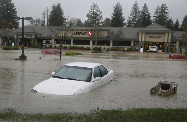 A car and shopping cart are submerged in water at a flooded shopping center Thursday, Dec. 11, 2014, in Healdsburg, Calif.  A powerful storm churned through Northern California Thursday, knocking  ...