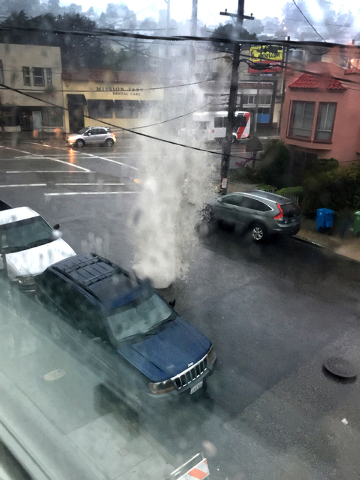 This photo provided by Robert Gower shows a manhole cover getting blown out by water rushing under a street in San Francisco street on Thursday, Dec. 11, 2014. A powerful storm churned through Nor ...