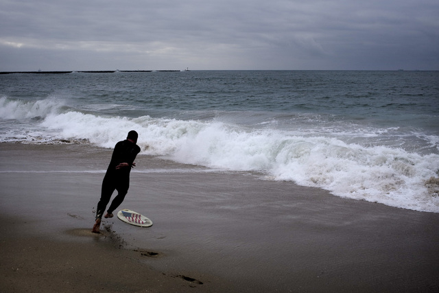 Sean Newton rides a skim board at the beach Thursday, Dec. 11, 2014, in Seal Beach, Calif. High winds and heavy rains caused flooding and landslides in the Pacific Northwest on Wednesday, and the  ...