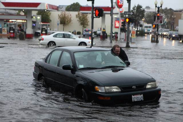 Mark Kunze of San Bruno pushes his stalled vehicle out of the flooded intersection of Airport Blvd. and Grand Ave. in South San Francisco, on Thursday, Dec. 11, 2014. Several vehicles stalled in a ...