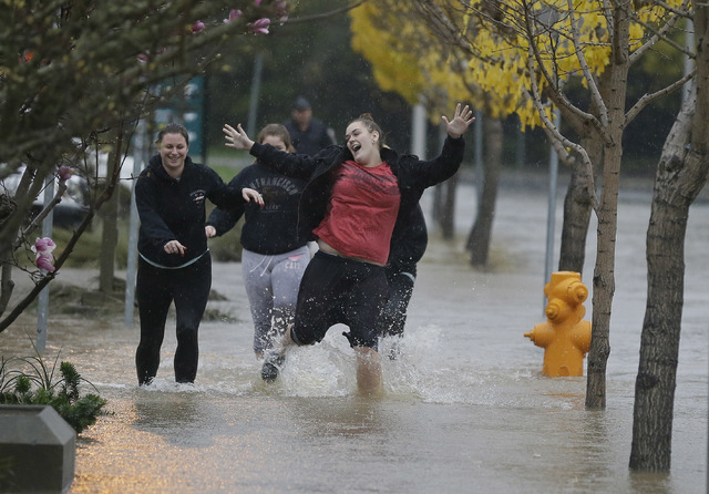 A group of girls laugh while running down a flooded street Thursday, Dec. 11, 2014, in Healdsburg, Calif.  A powerful storm churned through Northern California Thursday, knocking out power to tens ...