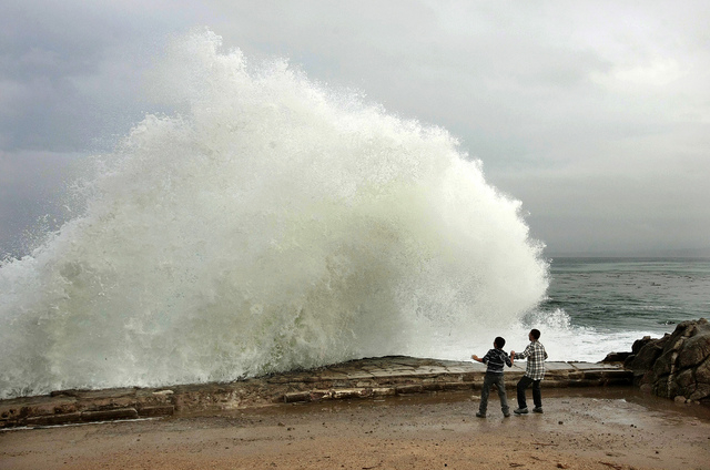 Aidan Stephenson,12, and Conor Stephenson,10, visiting from Phoenix, watch the waves break on Ocean View Blvd., Wednesday, Dec. 10, 2014, in Pacific Grove, Calif. Northern California residents are ...
