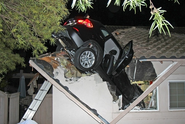 This photo provided by homeowner George Strother shows a sport utility vehicle that went airborne and sailed into the roof of his home in Escondido, Calif., around 12:30 a.m. Wednesday, Dec. 10, 2 ...