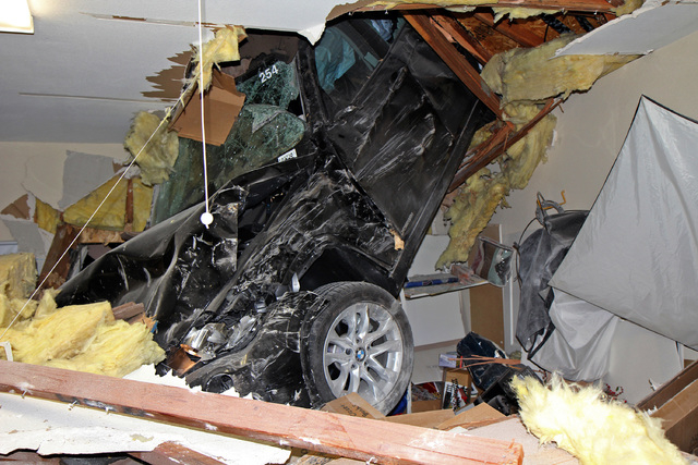This photo provided by homeowner George Strother shows a sport utility vehicle that went airborne and sailed into the roof of his home in Escondido, Calif., around 12:30 a.m.  (AP Photo/George Str ...
