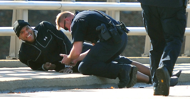 A Charlotte-Mecklenburg police officer tends to Carolina Panthers NFL football quarterback Cam Newton following a two-vehicle crash not far from the team's stadium in Charlotte, N.C., Tuesday, Dec ...