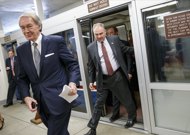 Sen. Edward Markey, D-Mass., left, and Sen. Tim Kaine, D-Va., join other senators in a rush to the Senate floor on Capitol Hill in Washington, Thursday, Dec. 11, 2014, for a procedural vote to adv ...