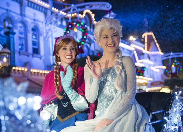 This Nov. 6, 2014 photo shows characters Princess Anna, left, and Queen Elsa during the festive procession, Mickey's Once Upon a Christmastime Parade, at Magic Kingdom in Lake Buena Vista, Fla. At ...