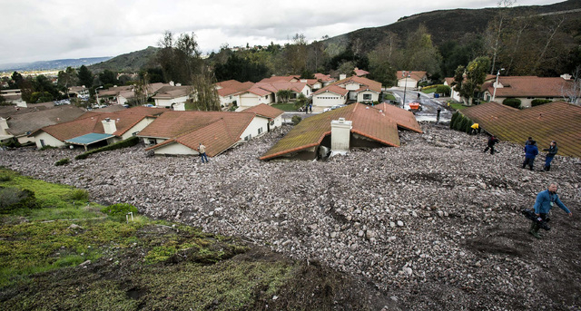 Debris and rocks fill the backyards of homes along San Como Lane in Camarillo Springs, Calif., after a storm on Friday, Dec. 12, 2014. Mountainsides stripped bare by a wildfire last year belched a ...