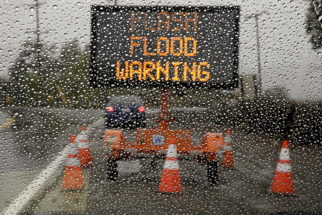 A sign warning of floods stands at the entrance to Silverado Canyon due to the potential for mud slides at a recent burn area Friday, Dec. 12, 2014 in Silverado Canyon, Calif. Silverado Canyon is  ...
